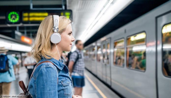 Frau mit Kopfhörern am Zug