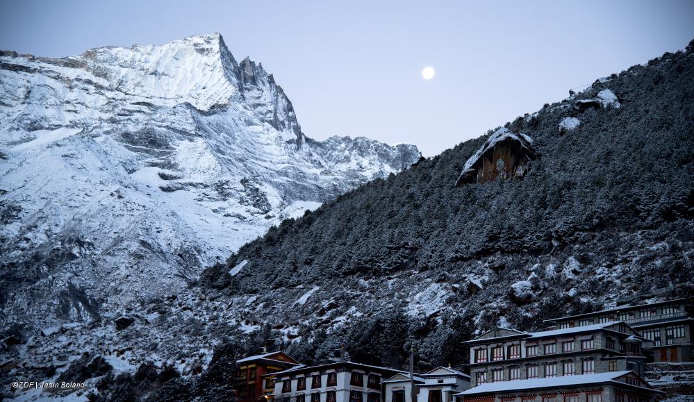 """""""Everest"""": Man sieht ein Dorf, das am Fuß eines schneebedeckten Berges liegt"""